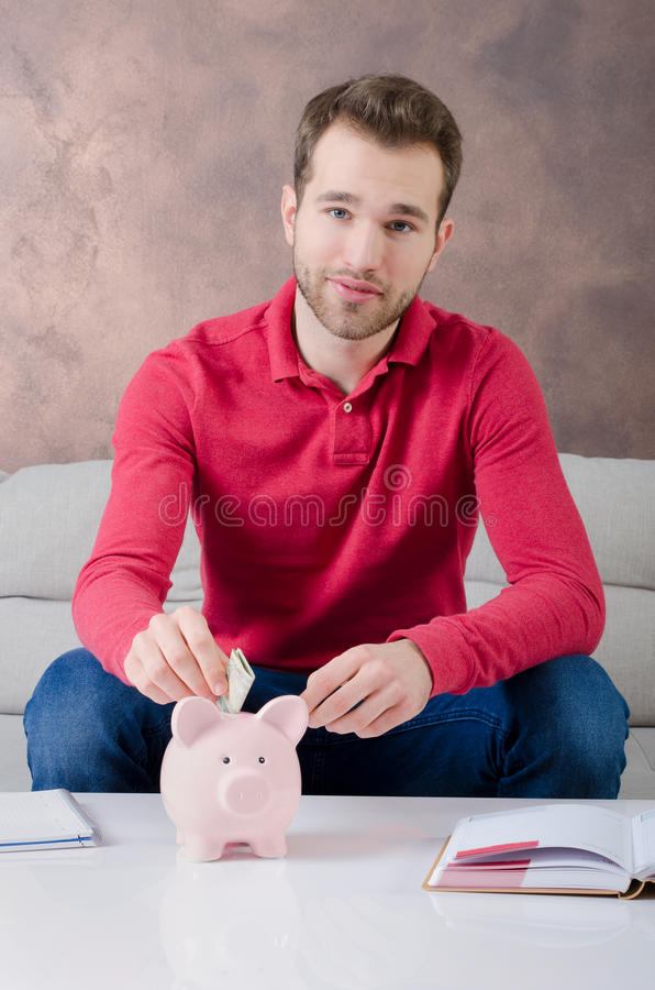 Den unga mannen sätter besparingar in i spargrisen royaltyfri fotografi