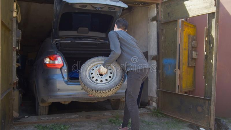 Den unga mannen sätter ett hjul i bilstam i garaget arkivbild