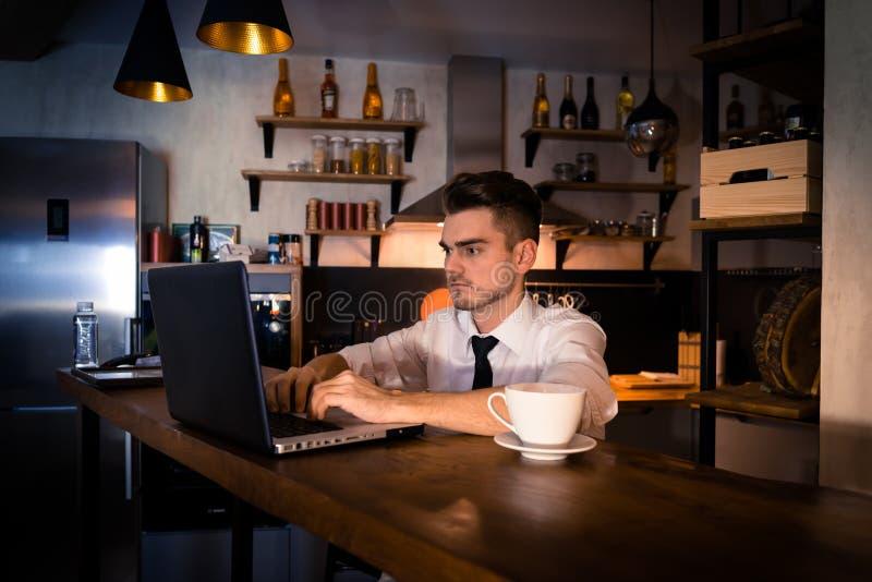 Den unga mannen sitter i köket på stångräknaren och arbetar i bärbar dator royaltyfri fotografi