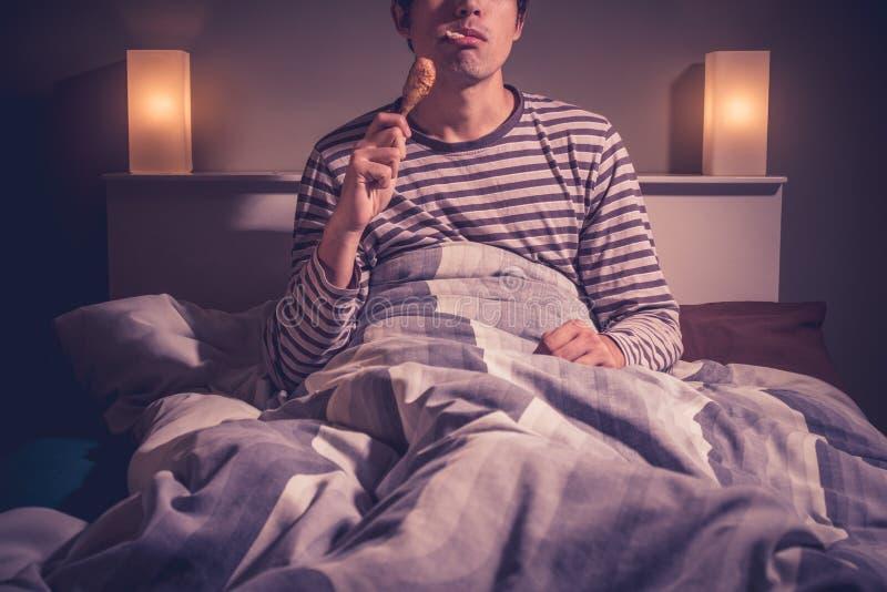 Den unga mannen sitter i säng och äter höna royaltyfri foto