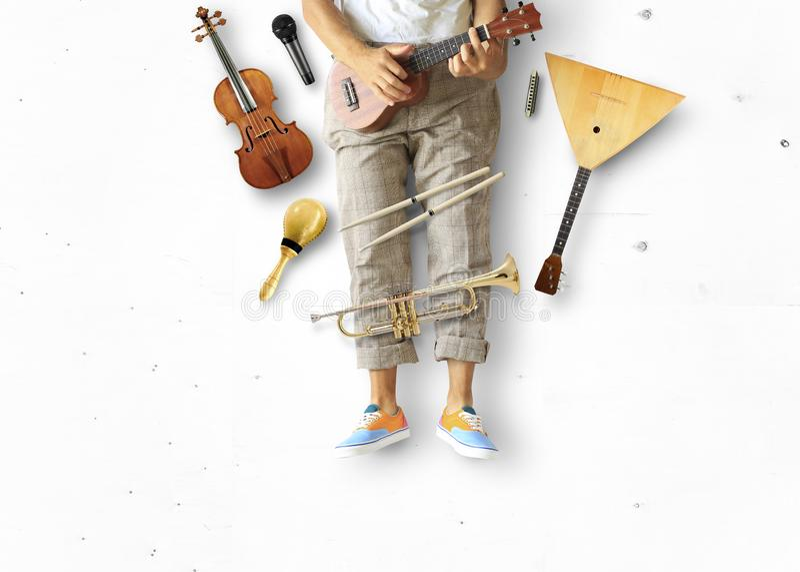 Den unga mannen sitter och spelar gitarren arkivbild
