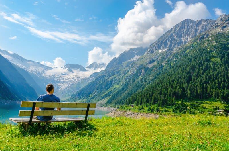 Den unga mannen sitter på bänk vid den azura bergsjön arkivfoto