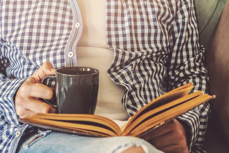 Den unga mannen sitter på en soffa och läser en bok, medan rymma en kopp kaffe eller ett te arkivfoto