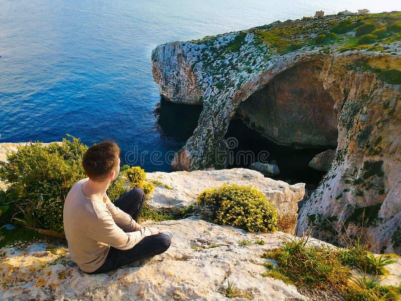 Den unga mannen sitter på kanten av en klippa och beundrar havet och stenarna royaltyfria foton