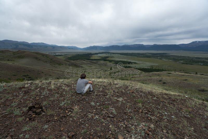 Den unga mannen sitter på kullen arkivfoton