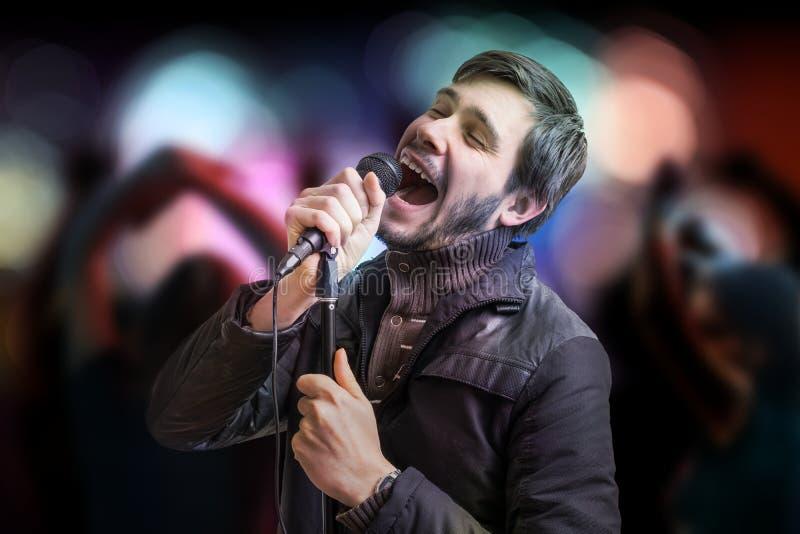 Den unga mannen sjunger en sång, och folket dansar i klubba arkivbilder