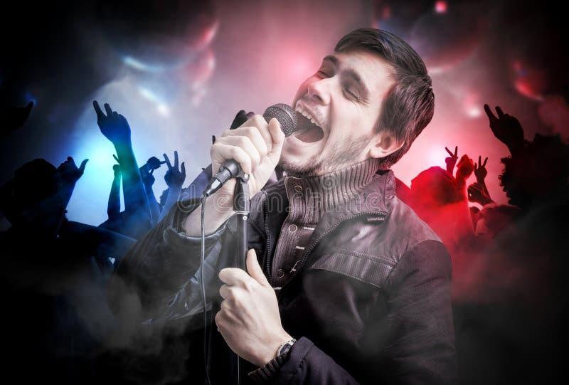 Den unga mannen sjunger en somg i diskoklubba Folket dansar i nattklubb fotografering för bildbyråer