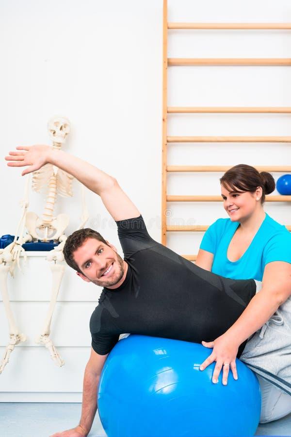 Den unga mannen som övar på schweizare, klumpa ihop sig i sjukgymnastik arkivfoto