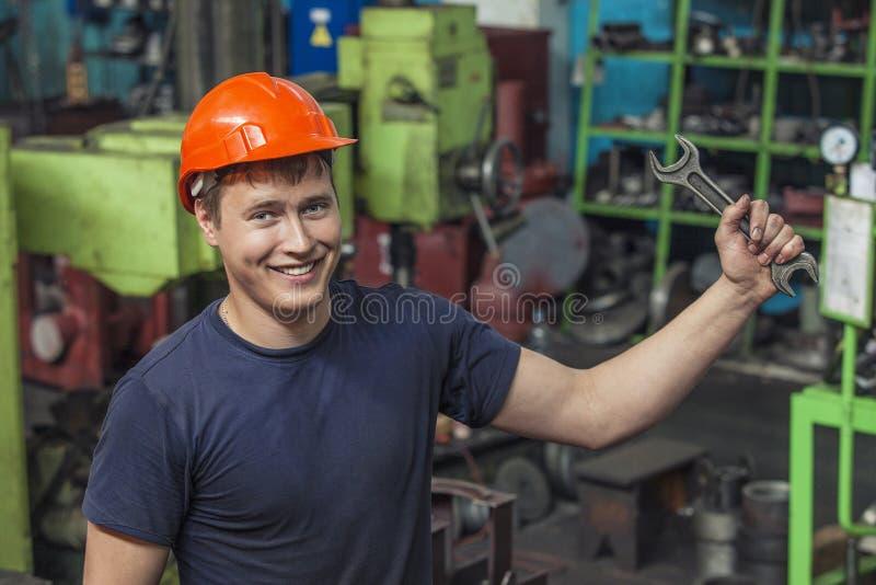 Den unga mannen som arbetar på den gamla fabriken på installation av equien royaltyfria foton