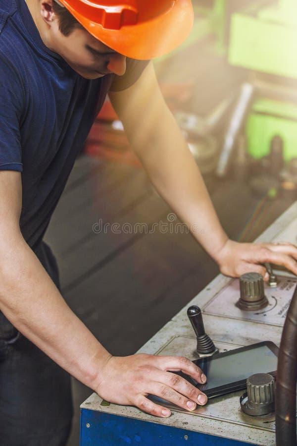 Den unga mannen som arbetar på den gamla fabriken på installation av equien royaltyfri foto
