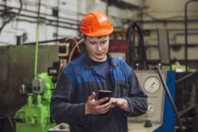 Den unga mannen som arbetar på den gamla fabriken på installation av equien royaltyfria bilder