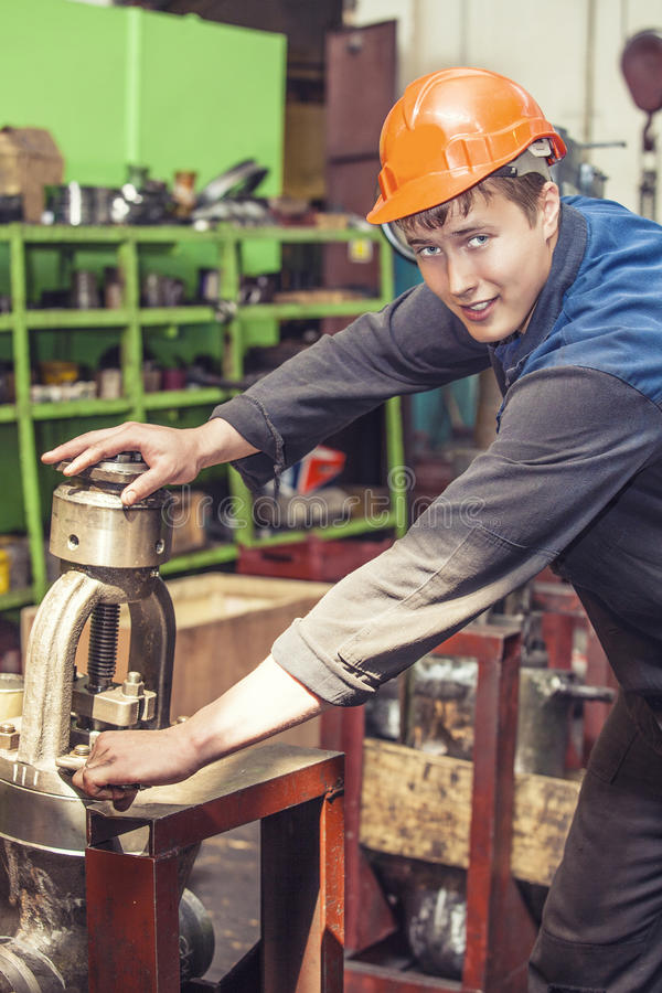 Den unga mannen som arbetar på den gamla fabriken på installation av equien arkivfoton