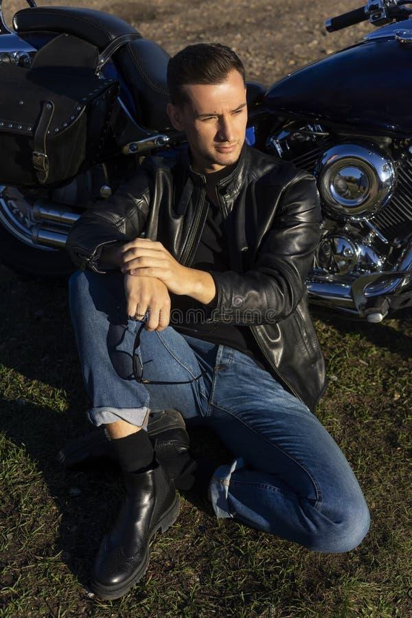 Den unga mannen som bär ett svart läderomslag och jeans, sitter utomhus- royaltyfria foton
