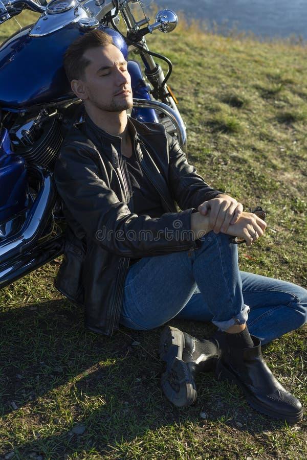 Den unga mannen som bär ett svart läderomslag och jeans, sitter utomhus- royaltyfria bilder
