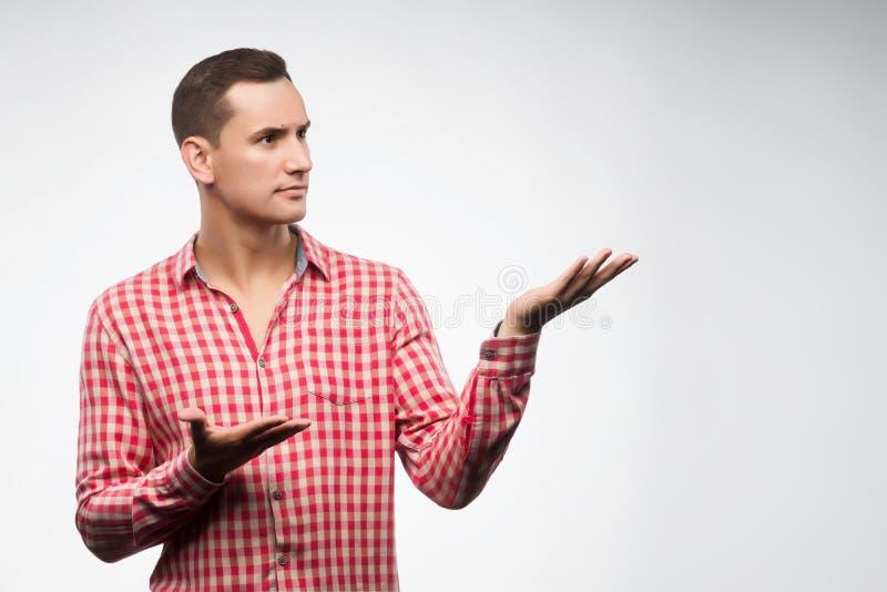 Den unga mannen som bär den rutiga röda skjortan, fördelar hans händer arkivfoton
