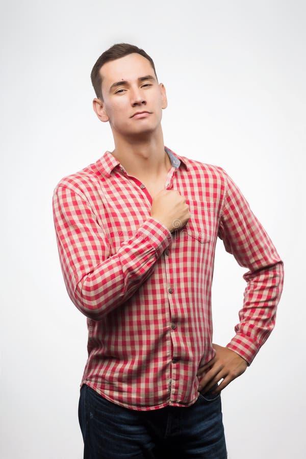 Den unga mannen som bär den rutiga röda skjortan, visar teckennäven till bröstkorgen royaltyfri bild
