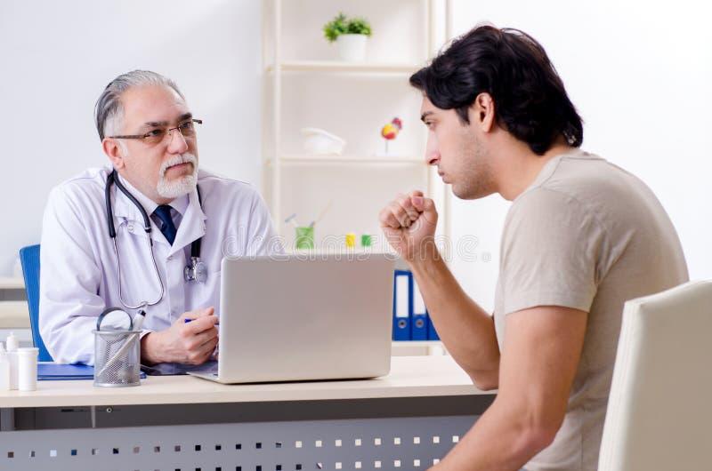 Den unga mannen som besöker den gamla manliga doktorn arkivbild