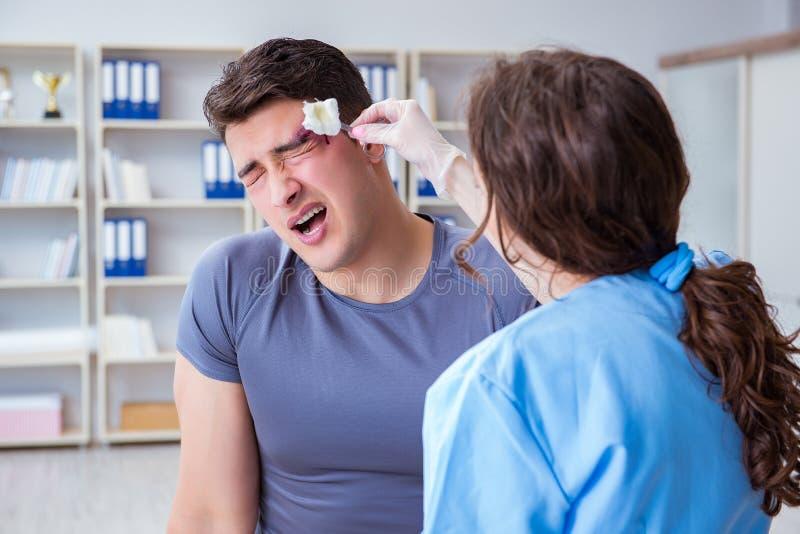 Den unga mannen som besöker den kvinnliga traumatologisten med blåtiran royaltyfria foton