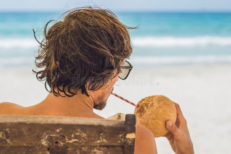 Den unga mannen som dricker kokosnöten, mjölkar på schäslong på stranden fotografering för bildbyråer