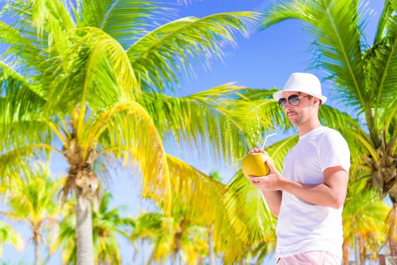 Den unga mannen som dricker kokosnöten, mjölkar på varm dag på stranden arkivbild
