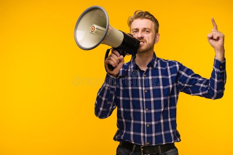 Den unga mannen som fotbollsfan med megafonen som isoleras på orange studio arkivfoto