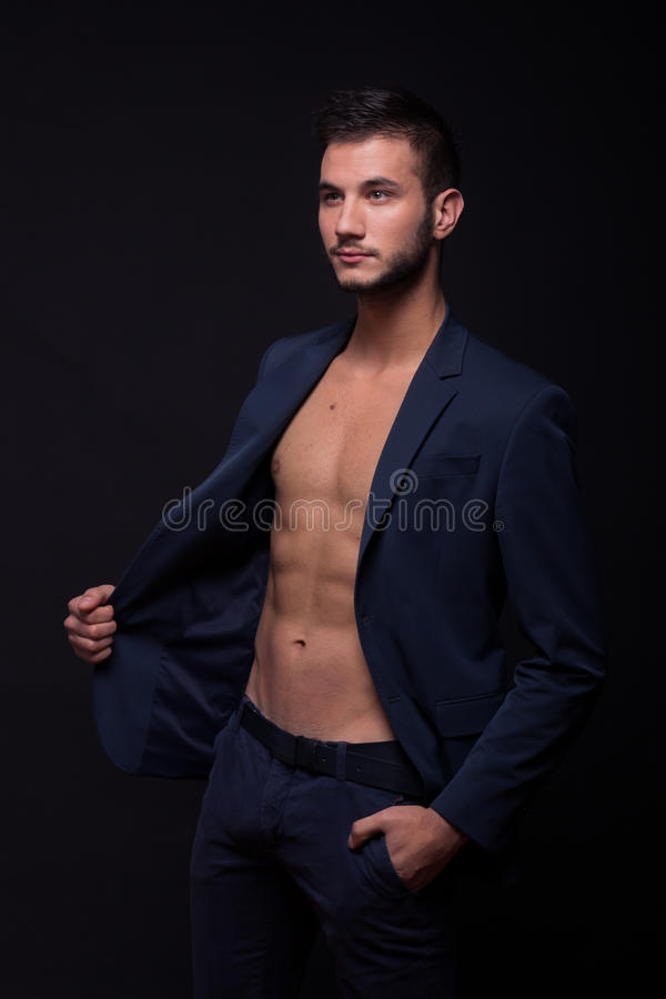 Den unga mannen som från sidan ser och att posera det shirtless dräktomslaget, flåsar arkivbilder
