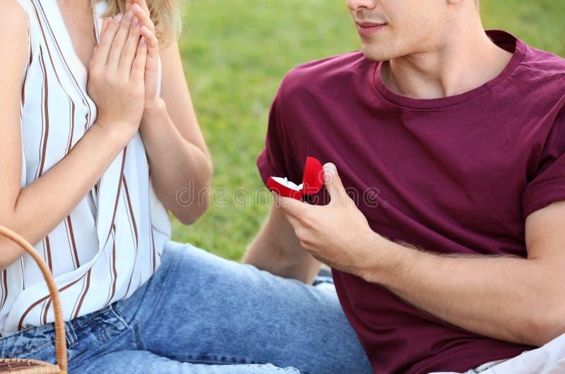 Den unga mannen som gör förslag till hans flickvän på romantiskt datum parkerar in royaltyfri foto