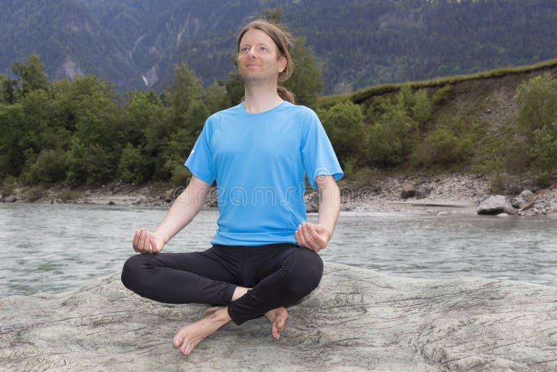 Den unga mannen som gör meditation i Lotus, poserar utomhus royaltyfri fotografi