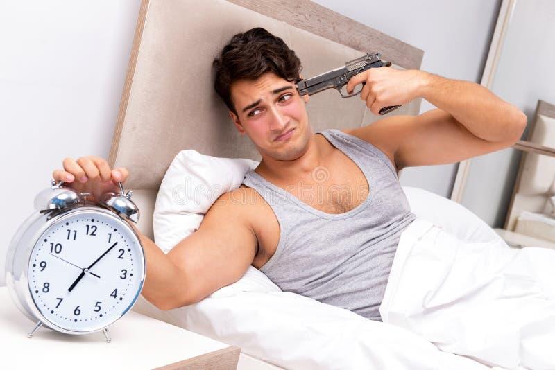 Den unga mannen som har problem som vaknar upp i morgonen royaltyfri foto
