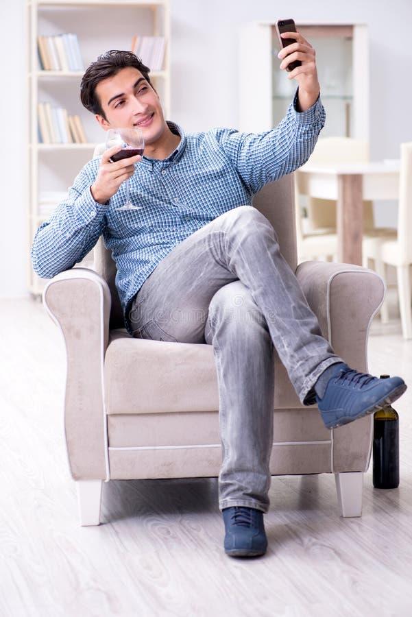 Den unga mannen som hemma dricker vin royaltyfri bild