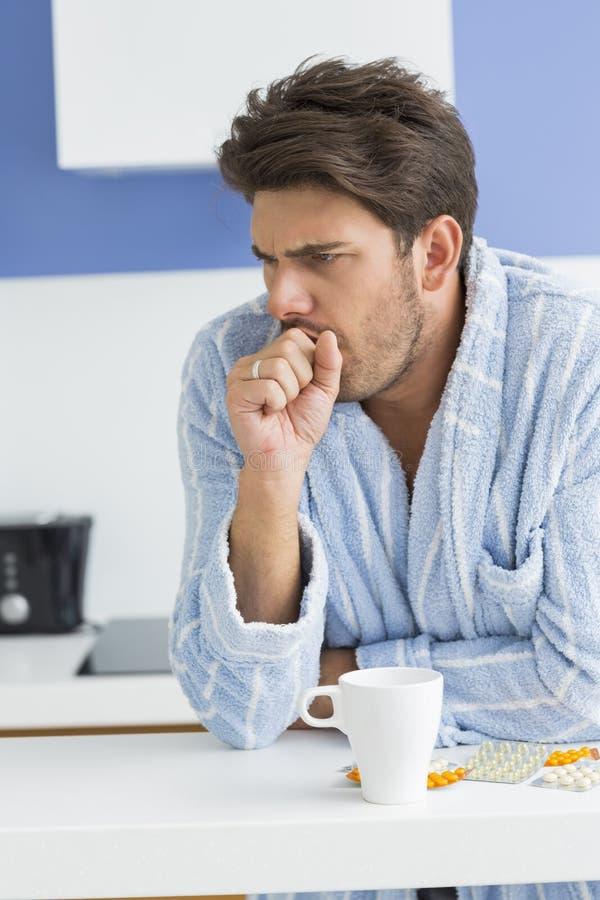 Den unga mannen som hostar med kaffe, rånar och medicin på diskbänken arkivbild