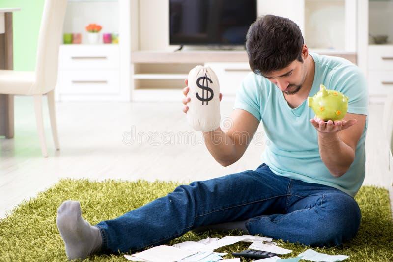 Den unga mannen som kämpar med personlig finans och räkningar arkivbild