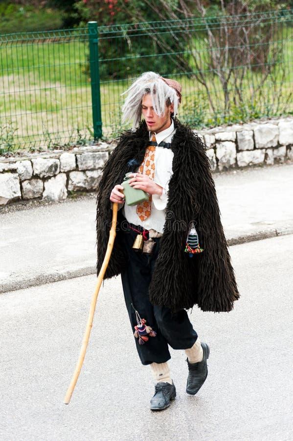 Den unga mannen som maskeras som en full bydumbom, deltar i maskeraden ståtar i Metkovic, Kroatien arkivfoton