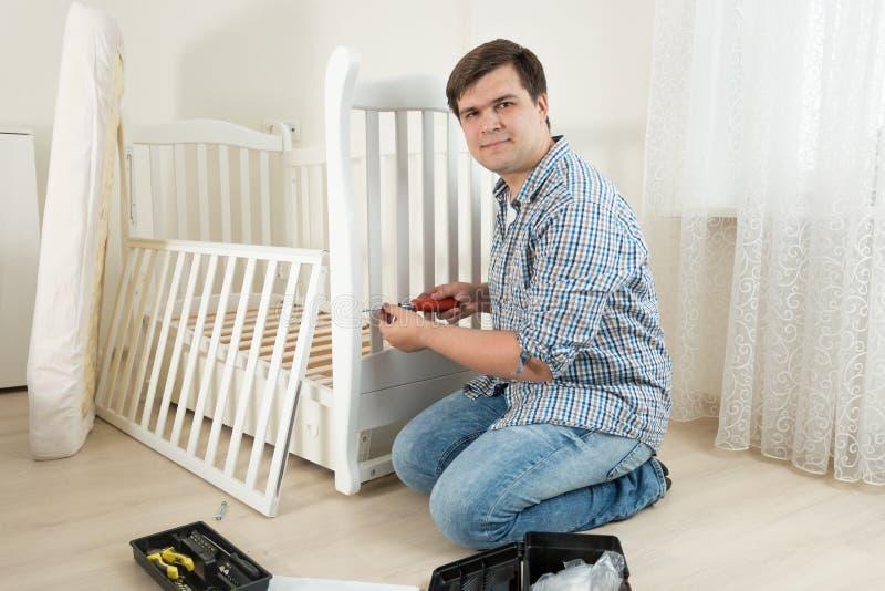Den unga mannen som monterar träkåtan i barnkammaren för förväntansfullt, behandla som ett barn arkivbild