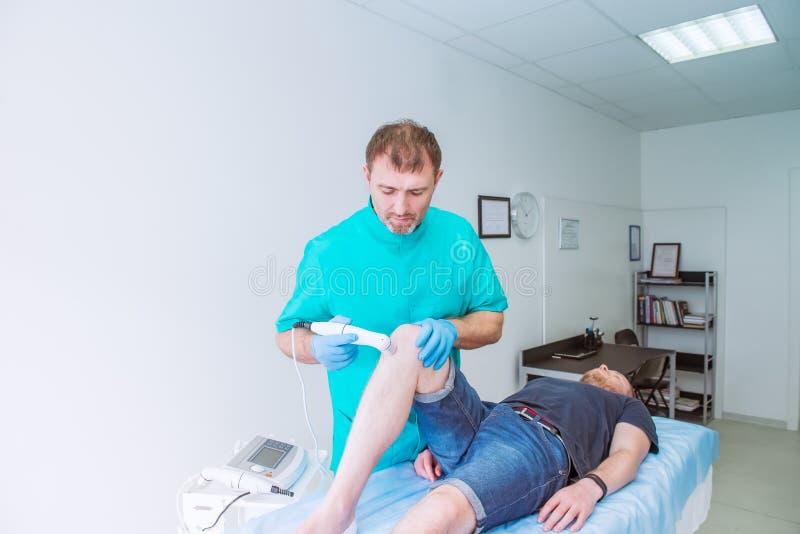 Den unga mannen som mottar laser, eller magnetterapimassagen på ett knä till mindre smärtar En kiropraktor behandlar patientens k royaltyfri fotografi
