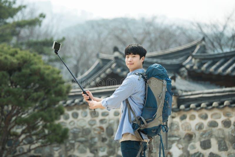 Den unga mannen, som reser till Korea, tar bilder genom att använda hans smartphone arkivbild
