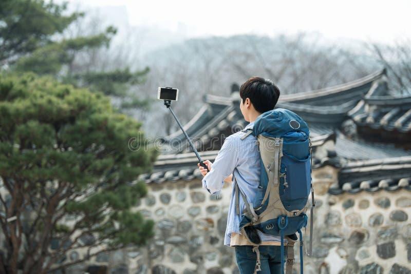 Den unga mannen, som reser till Korea, tar bilder genom att använda hans smartphone royaltyfri foto