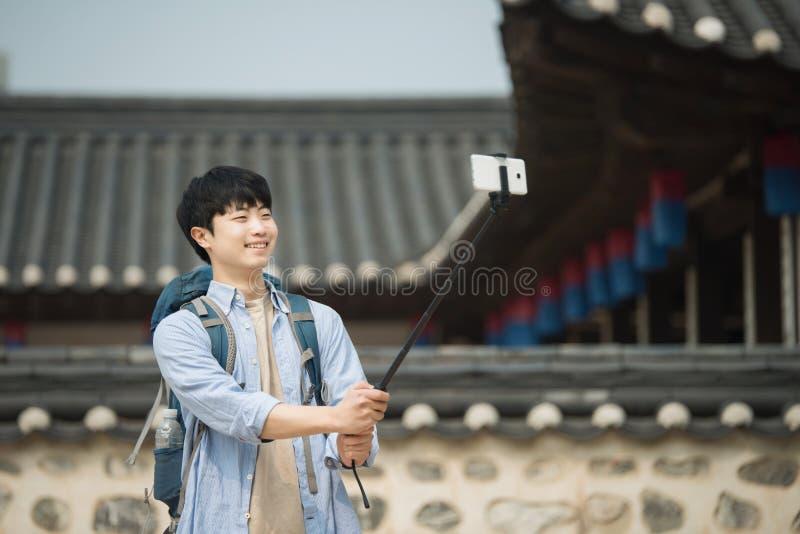 Den unga mannen, som reser till Korea, tar bilder genom att använda hans smartphone arkivfoton