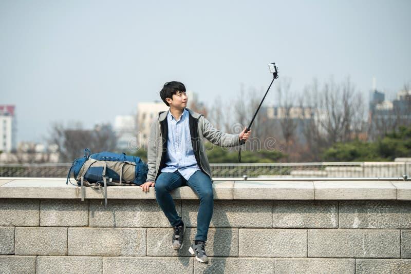 Den unga mannen, som reser till Korea, tar bilder genom att använda hans smartphone arkivbilder