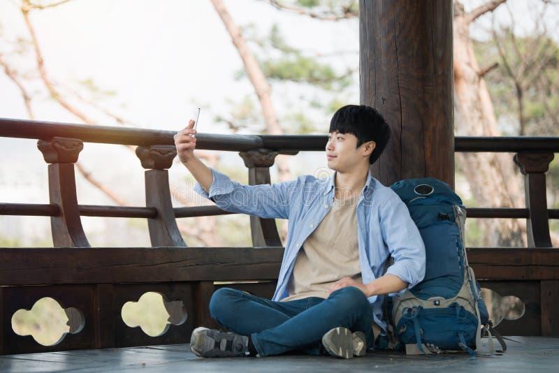 Den unga mannen, som reser till Korea, tar bilder genom att använda hans smartphone royaltyfri bild