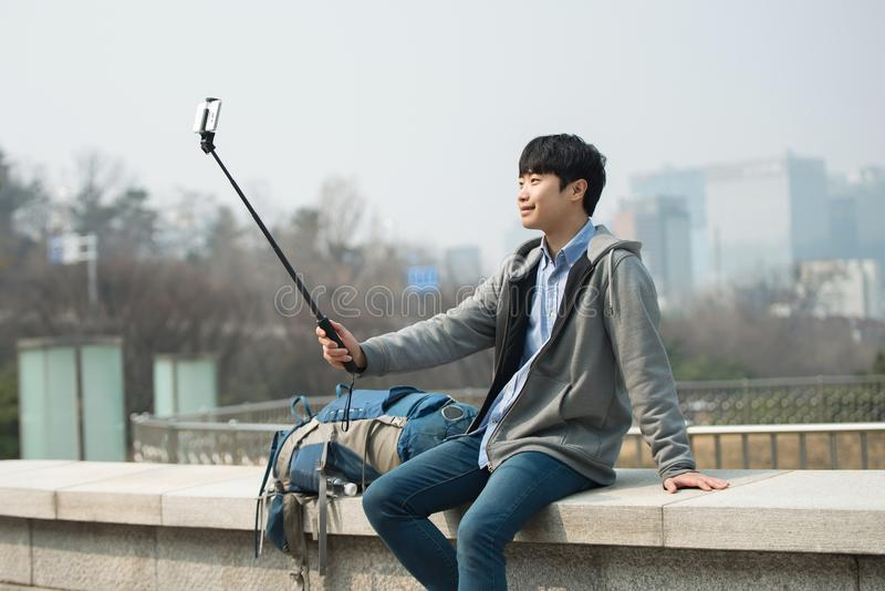 Den unga mannen, som reser till Korea, tar bilder genom att använda hans smartphone royaltyfria bilder