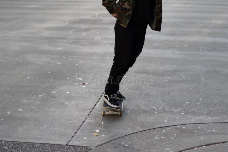Den unga mannen som rider hans skateboard på gummi, befläckte den konkreta körbanan arkivbild