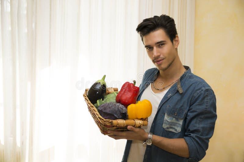 Den unga mannen som rymmer en korg av nya grönsaker som är sund bantar begrepp fotografering för bildbyråer