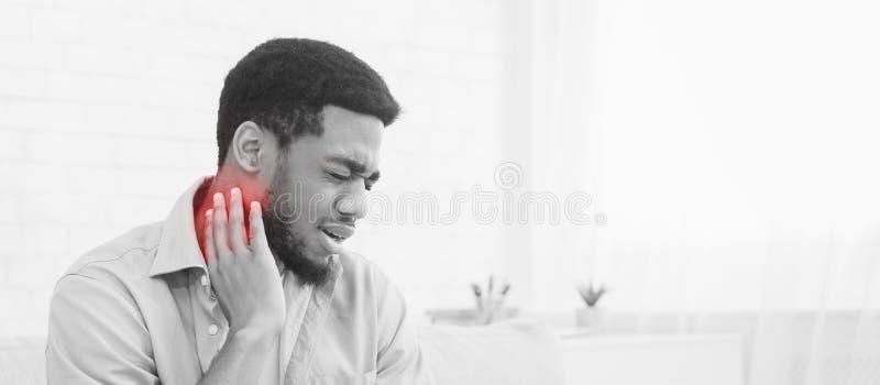 Den unga mannen som rymmer hans hals smärtar, kopierar in, utrymme arkivfoton