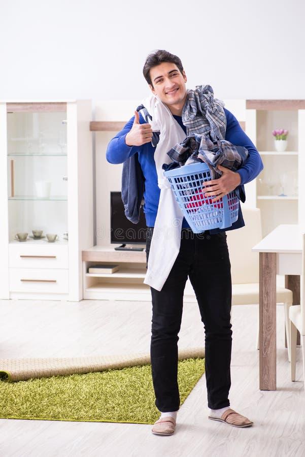 Den unga mannen som samlar smutsiga kläder för tvätteri royaltyfri bild