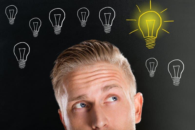 Den unga mannen som ser upp med den idérika ljusa kulan, skissar arkivfoto