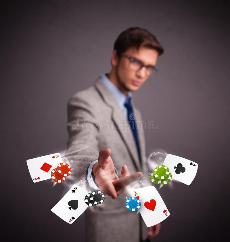 Den unga mannen som spelar med poker, cards och gå i flisor arkivbild