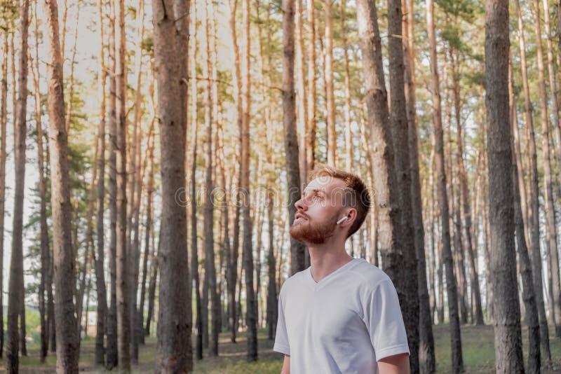 Den unga mannen som tycker om naturen under, går eller joggar i skogen royaltyfri fotografi