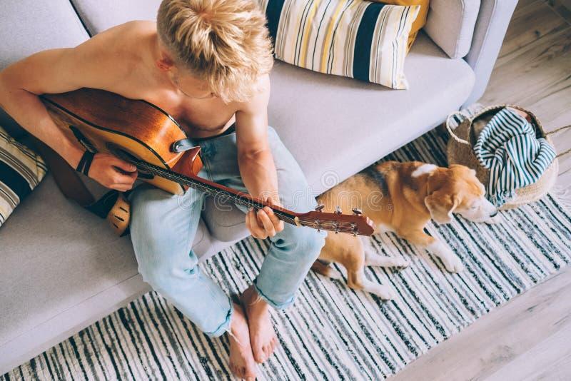 Den unga mannen spelar på gitarrsammanträde på soffan i hemtrevlig hem- atmosfär royaltyfri foto
