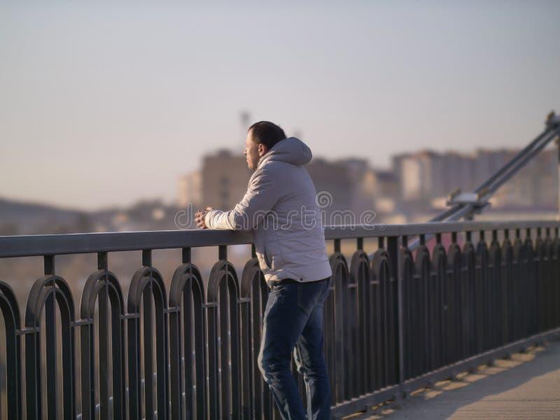 Den unga mannen står bara på en bro på en solig dag, bakre sikt fotografering för bildbyråer
